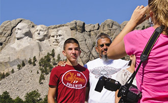 Family taking a picture with Mt. Rushmore in the background